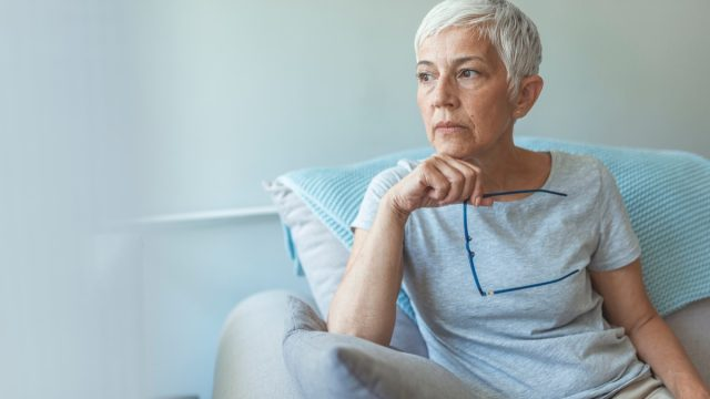 older woman sitting on the couch looking worried