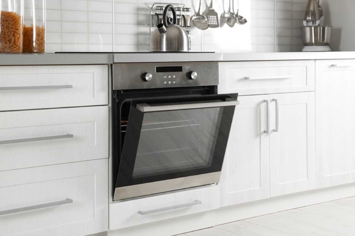 open stainless steel oven in a white modern kitchen, fire prevention tips