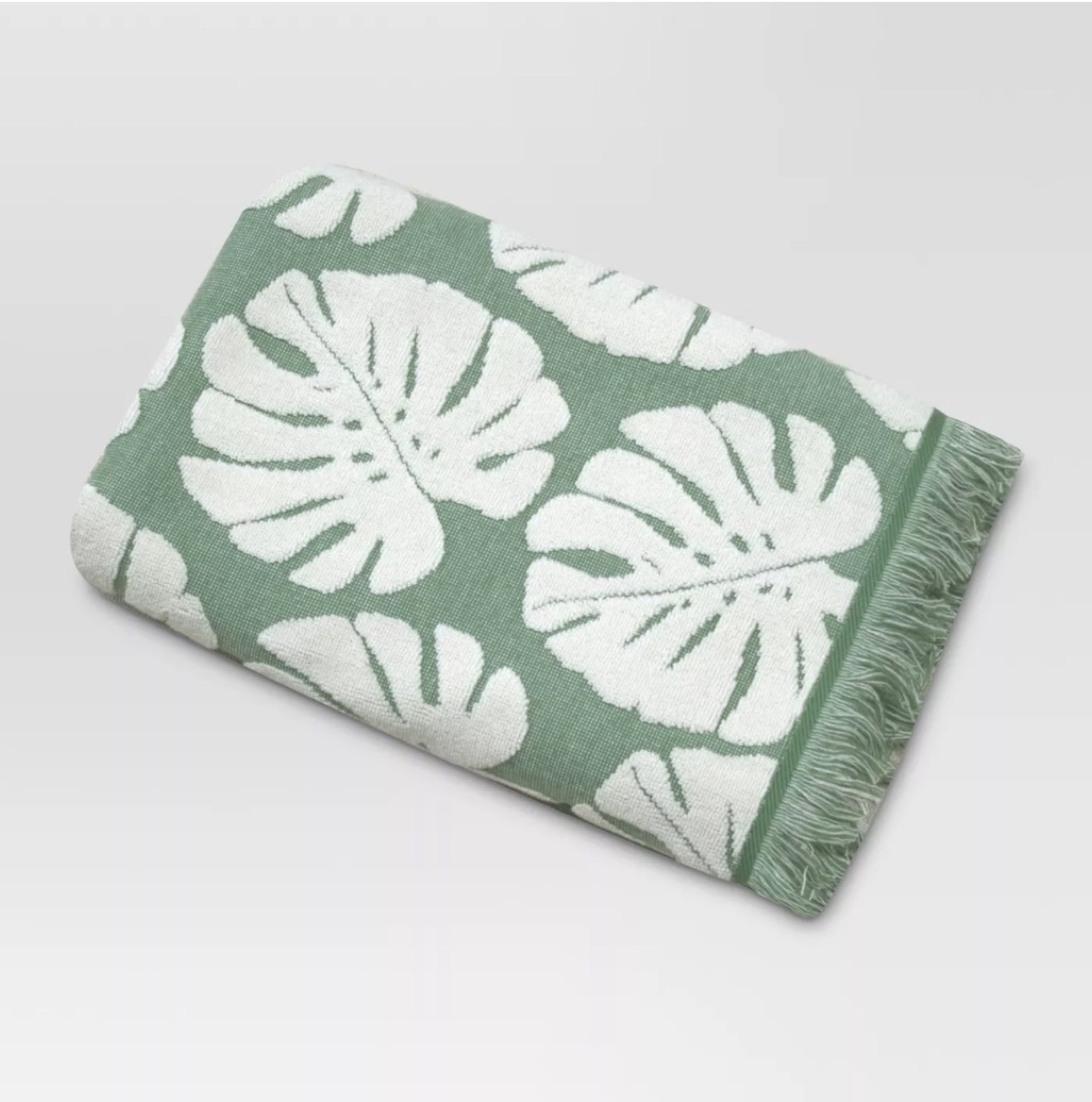 green bath towel with white leaves on it, bathroom accessories