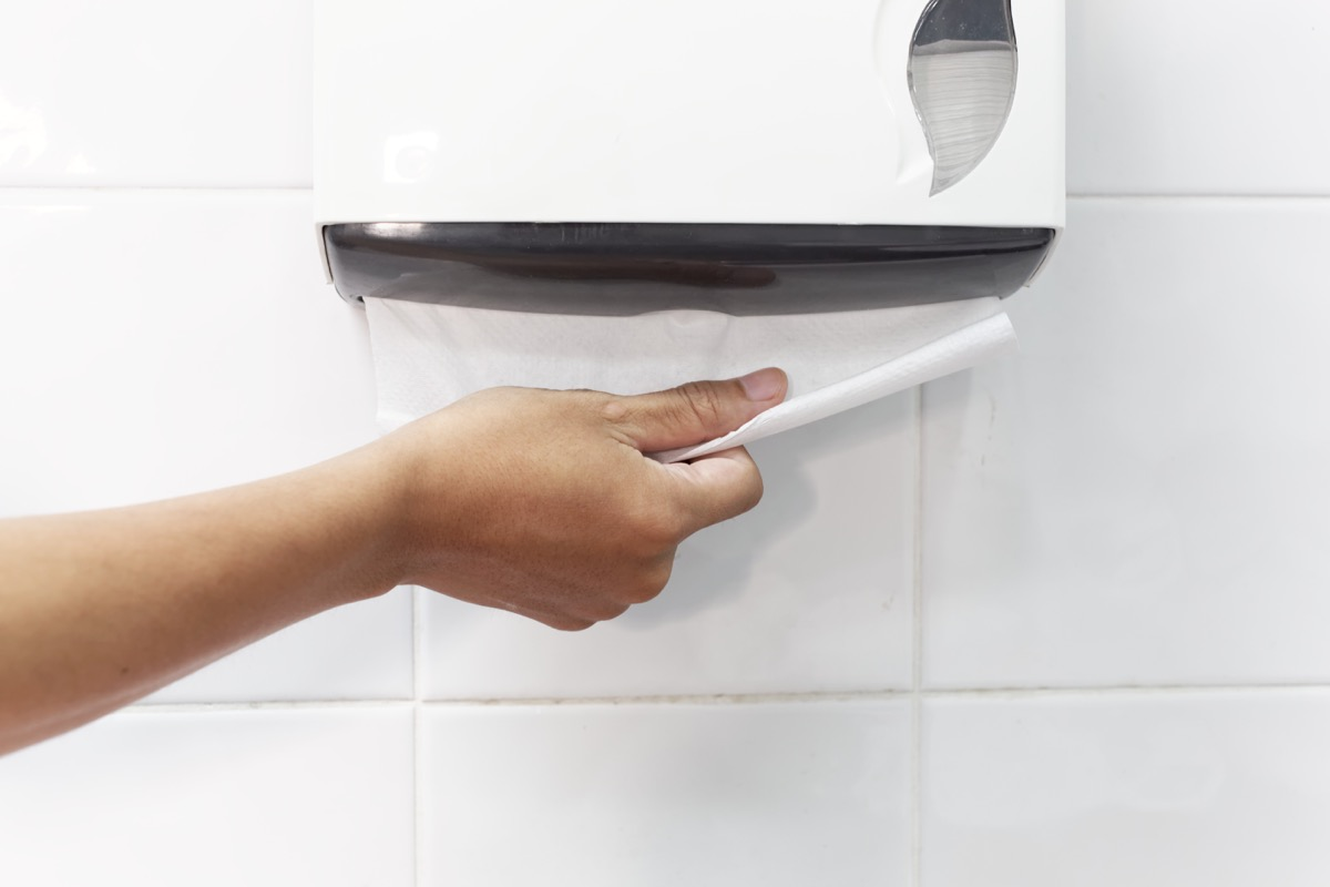 Person using a paper towel dispenser classroom surfaces germs
