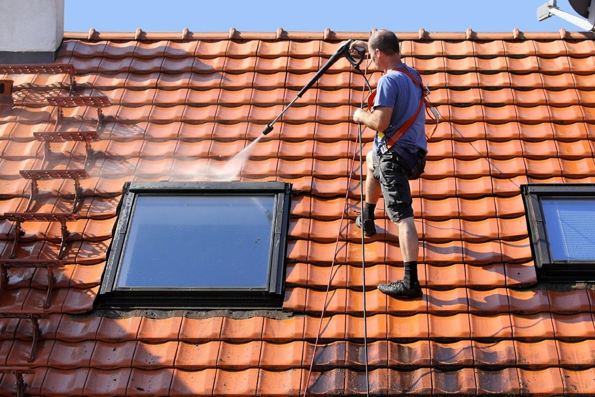 man power washing roof