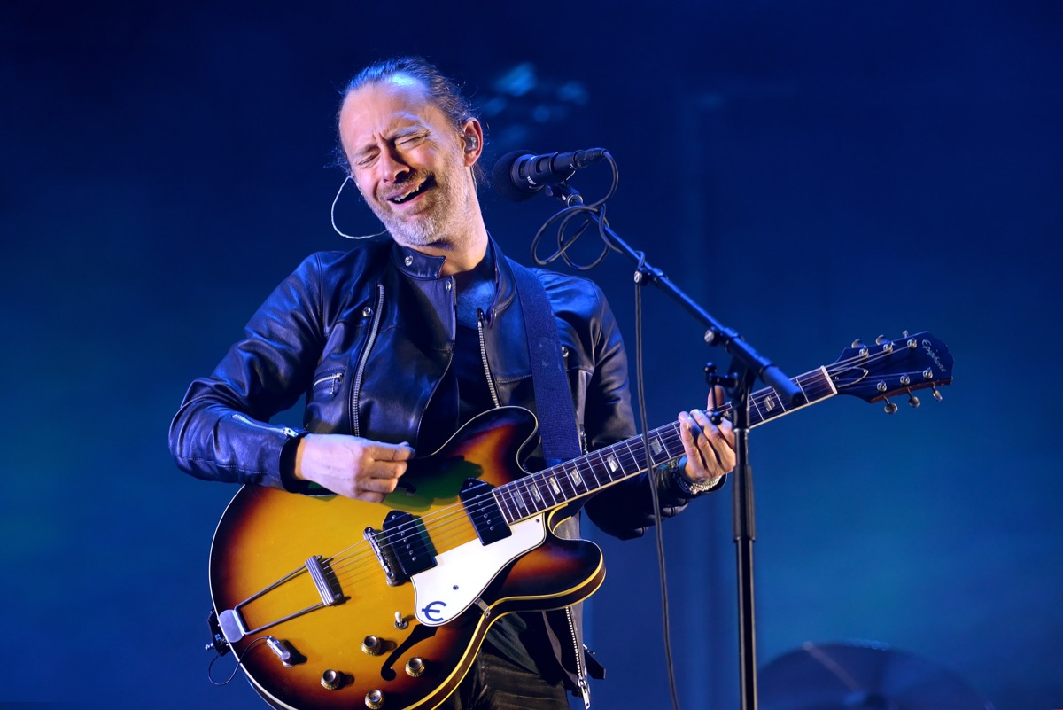 thom yorke playing guitar on stage during a radiohead set