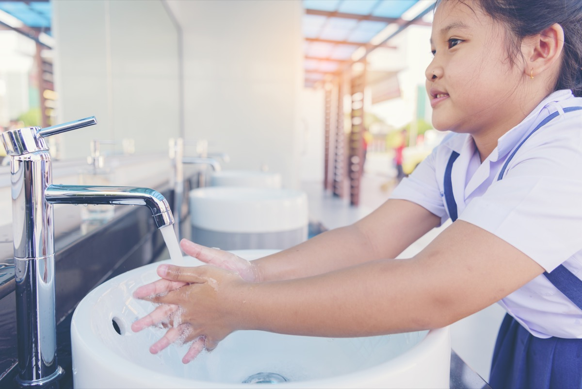 A little girl washing her hands in a school bathroom classroom surfaces germs