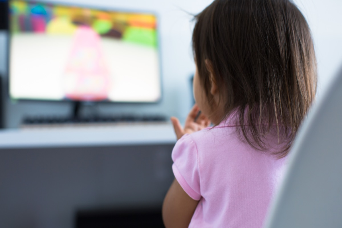 A 3-5 years old girl toddler sitting at the computer desk watching cartoon shows on the monitor at home. Children educational and development concept.