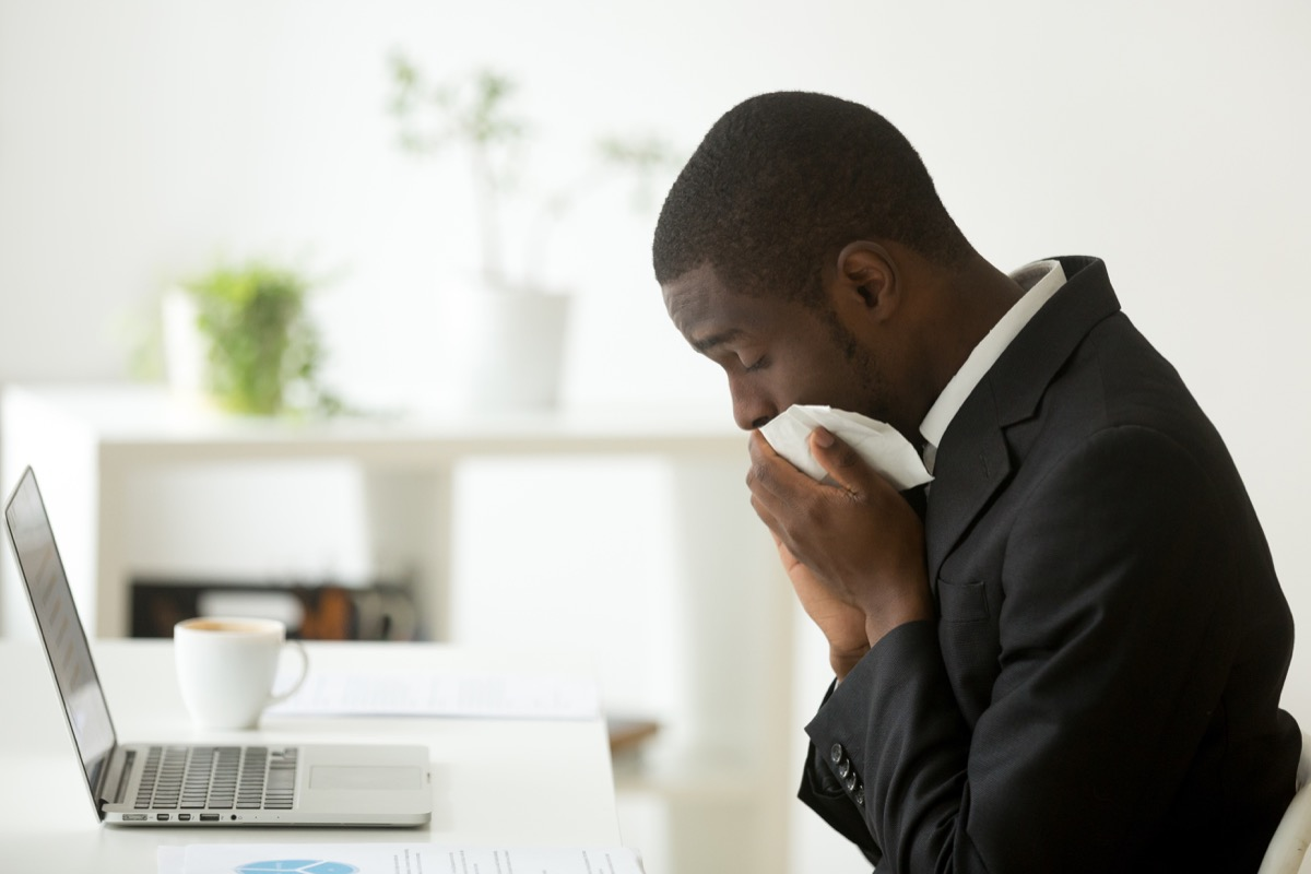 Man getting sick at his desk in his office