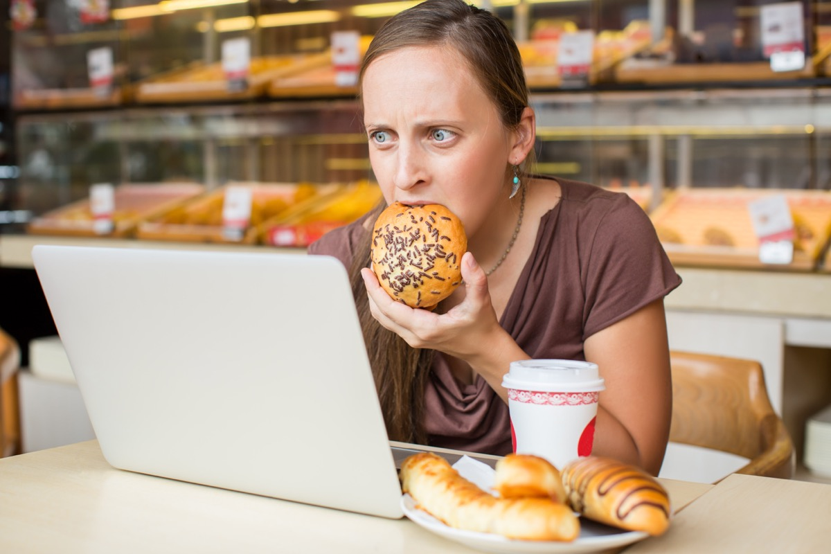 woman stress eating a piece of bread, stress signs