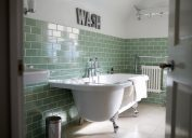 bathroom with freestanding tub and green subway tile, bathroom accessories