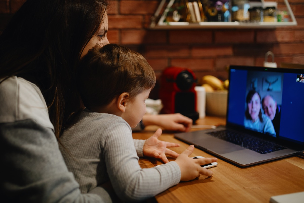 Grandparents in quarantine at home having video call with grandson and daughter