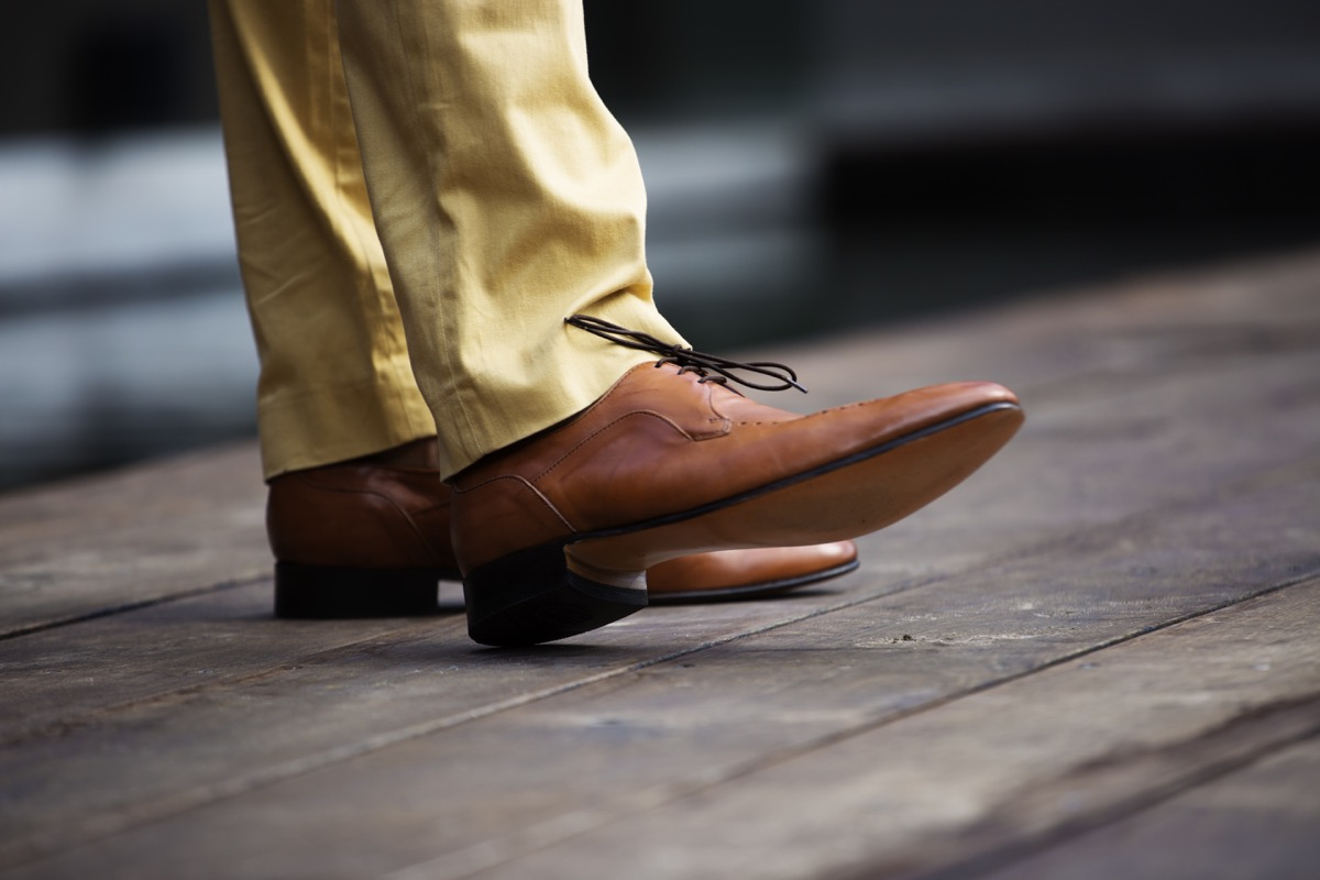 Mans legs in brown leather shoes shot from below the knee