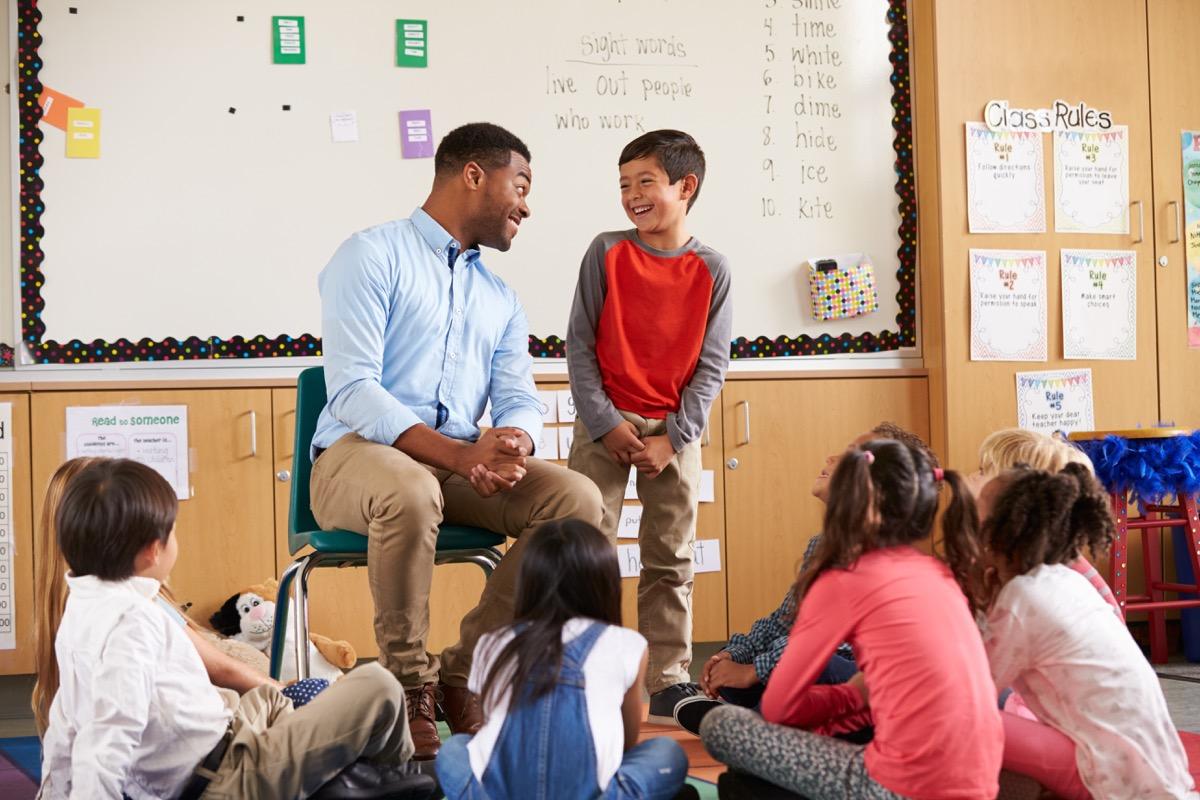 student talking to teacher as classmates listen in