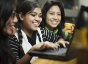 Indoor image of a group of late teen girls from different ethnicities using laptop together