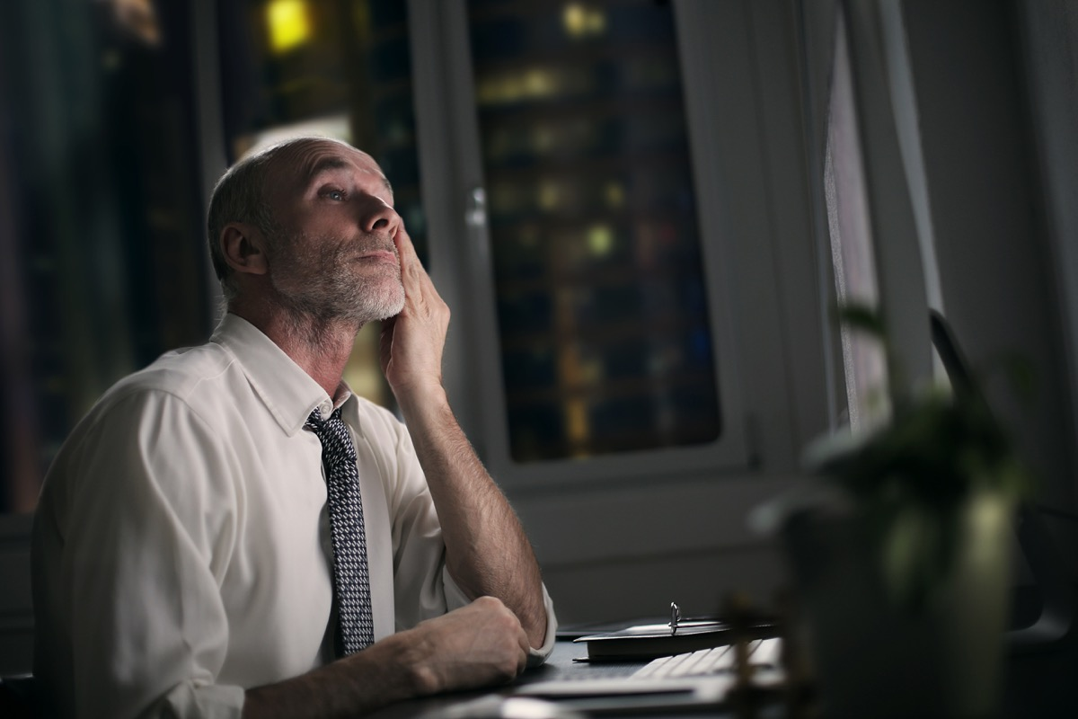 tired older man sitting in front of his computer