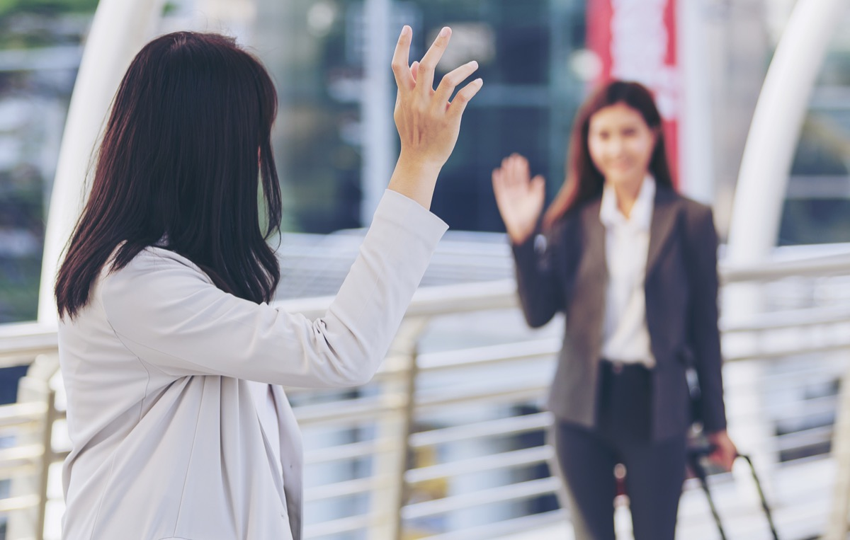 two woman waving hello in the street as they pass each other, old-fashioned etiquette rules
