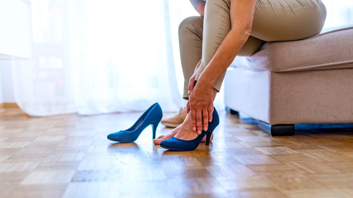 woman rubbing her feet in heels