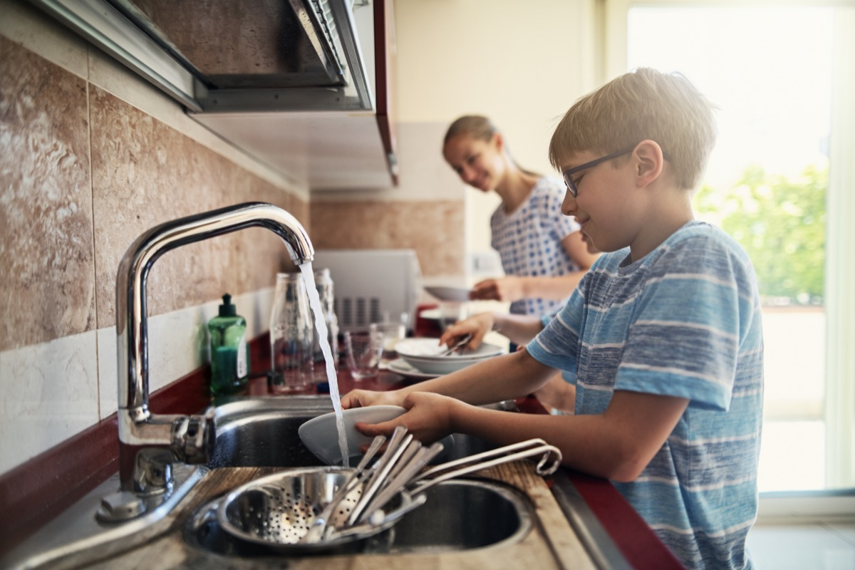 Three kids washing up dishes in kitchen. The boys and a girl are working together to help their parents.
