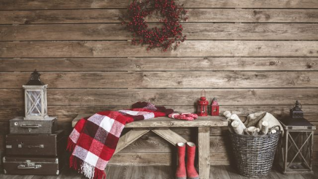 wooden wall with wreath and bench with blanket draped over it and red boots, rustic farmhouse decor
