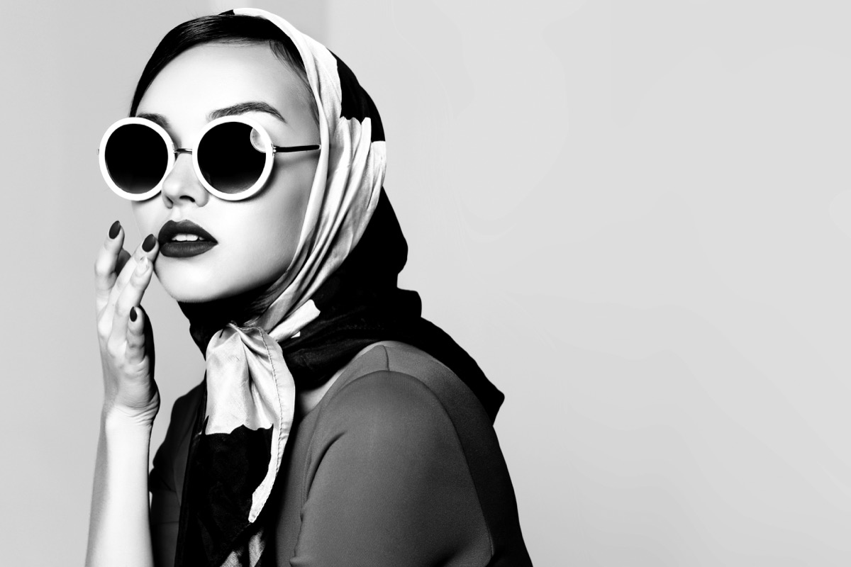 woman in big sunglasses and a headscarf in black and white vintage shot