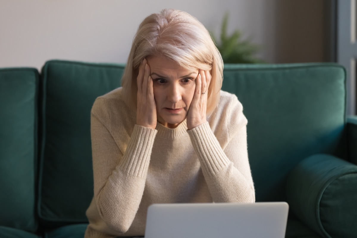 older woman angry in front of laptop