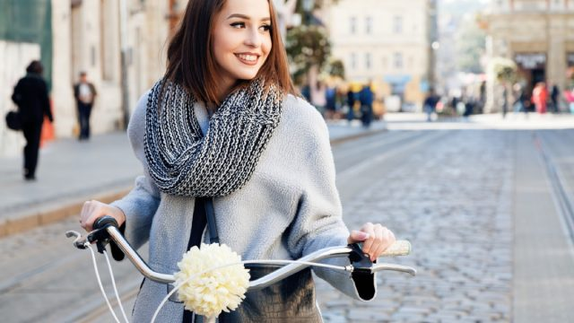 woman in gray coat on bicycle outside, best winter coats for women