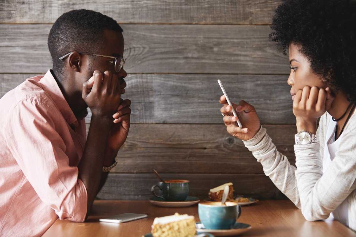 woman on the phone while a man is talking to her, stress signs