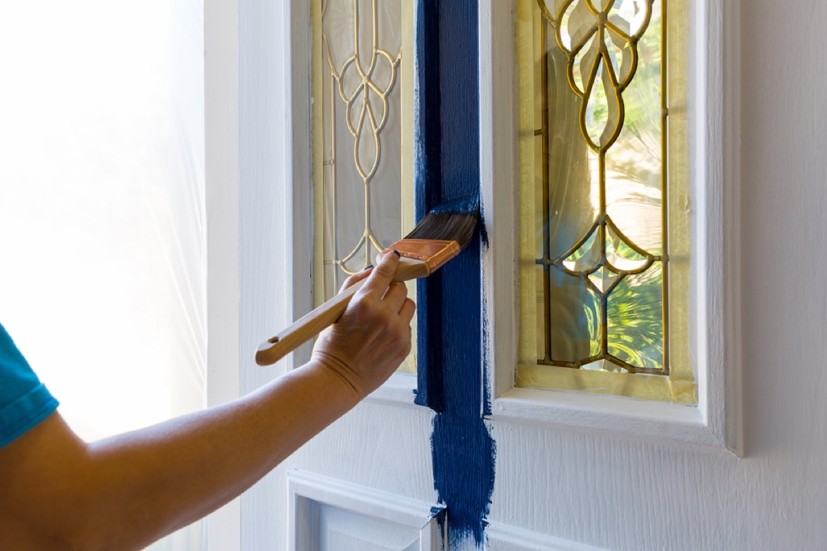 woman painting front door blue, worst things about the suburbs