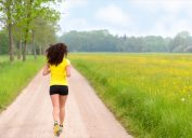 Woman running in a park or farmland area with nobody around town no traffic lights