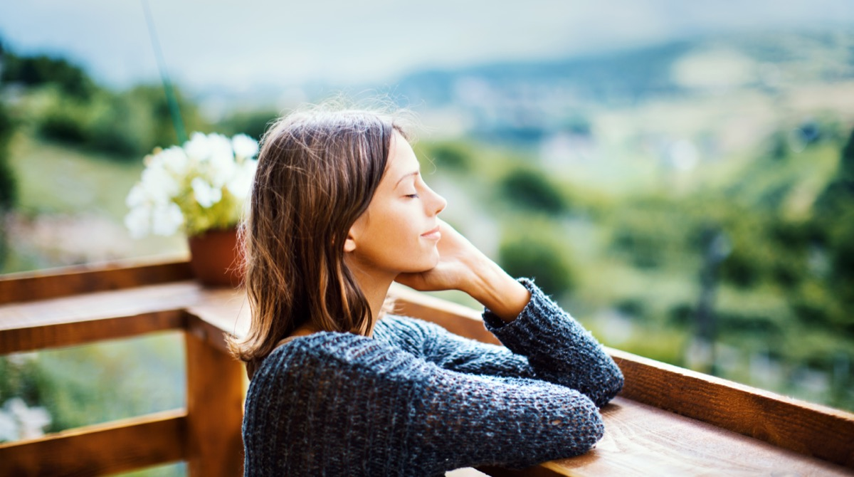 woman smiling with her eyes closed outside smelling fresh air