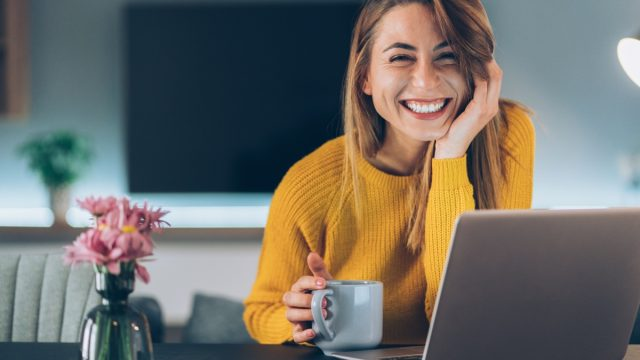 woman smiling while looking up from her laptop