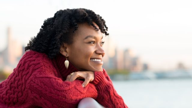 woman thinking and smiling on the side of a bridge