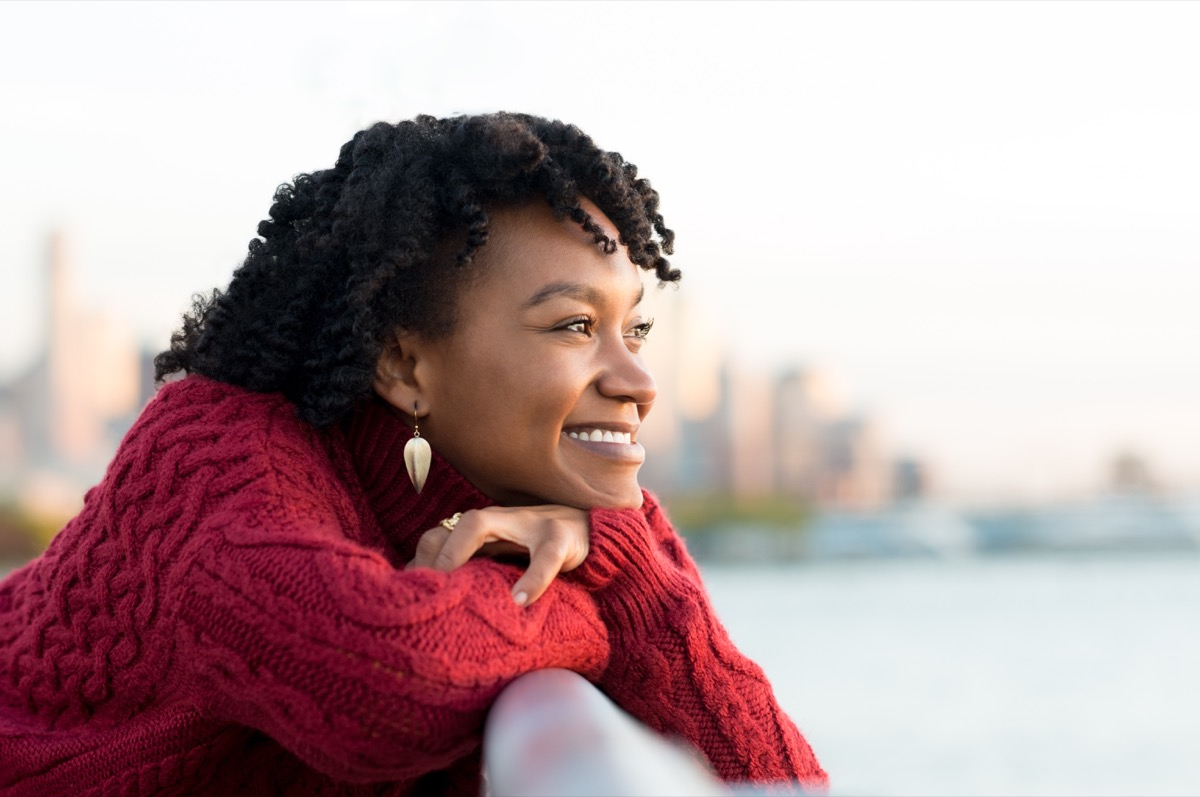 woman thinking and smiling on the side of a brige