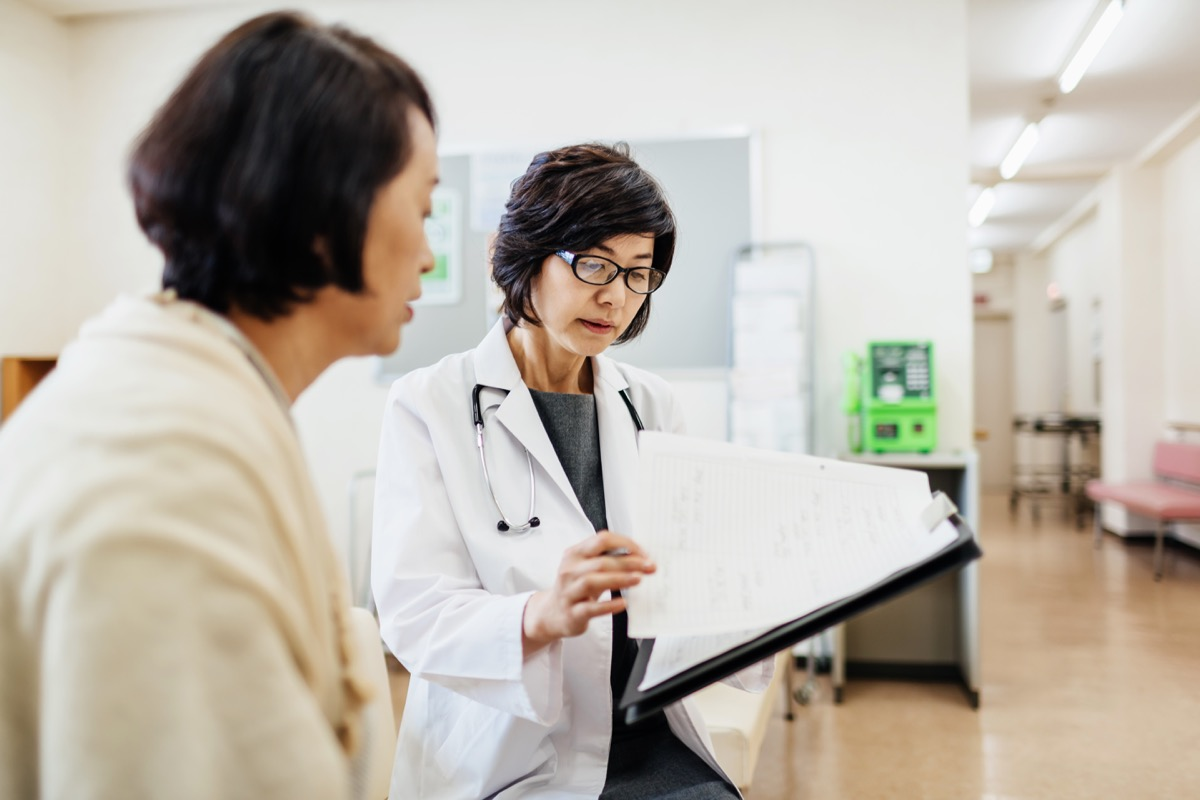 woman talking to her doctor in the waiting room with forms