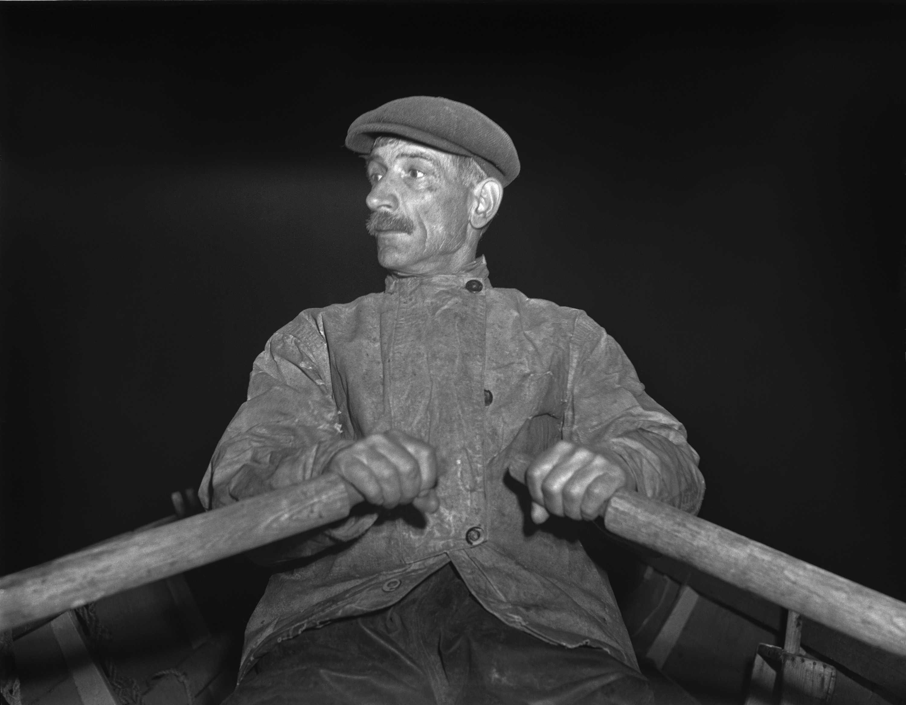 Fisherman rowing out to his boat early in the morning for the fishing banks off Cape Cod in 1942