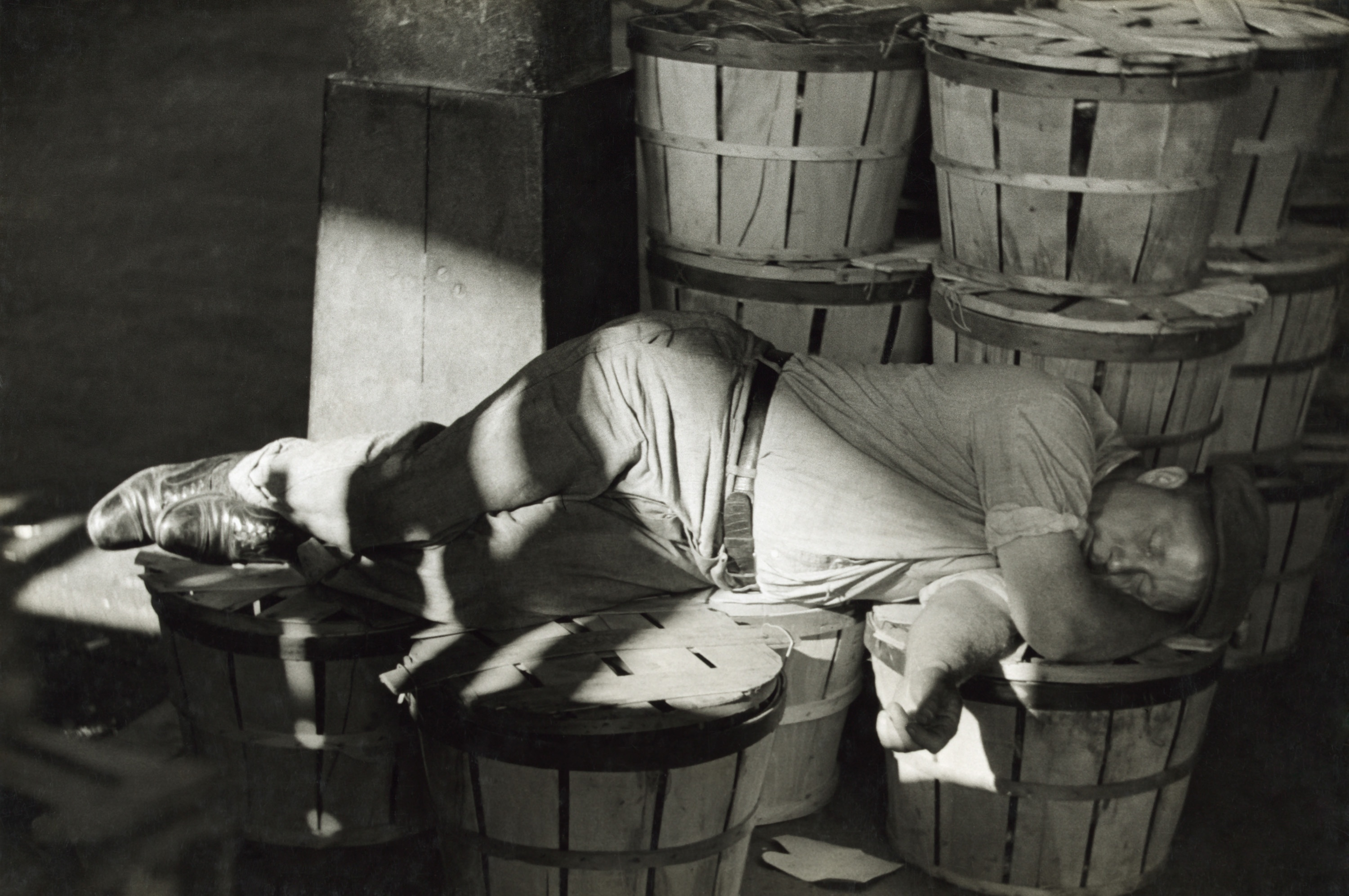 Workman catching a nap at the Baltimore fish market, July 1938.