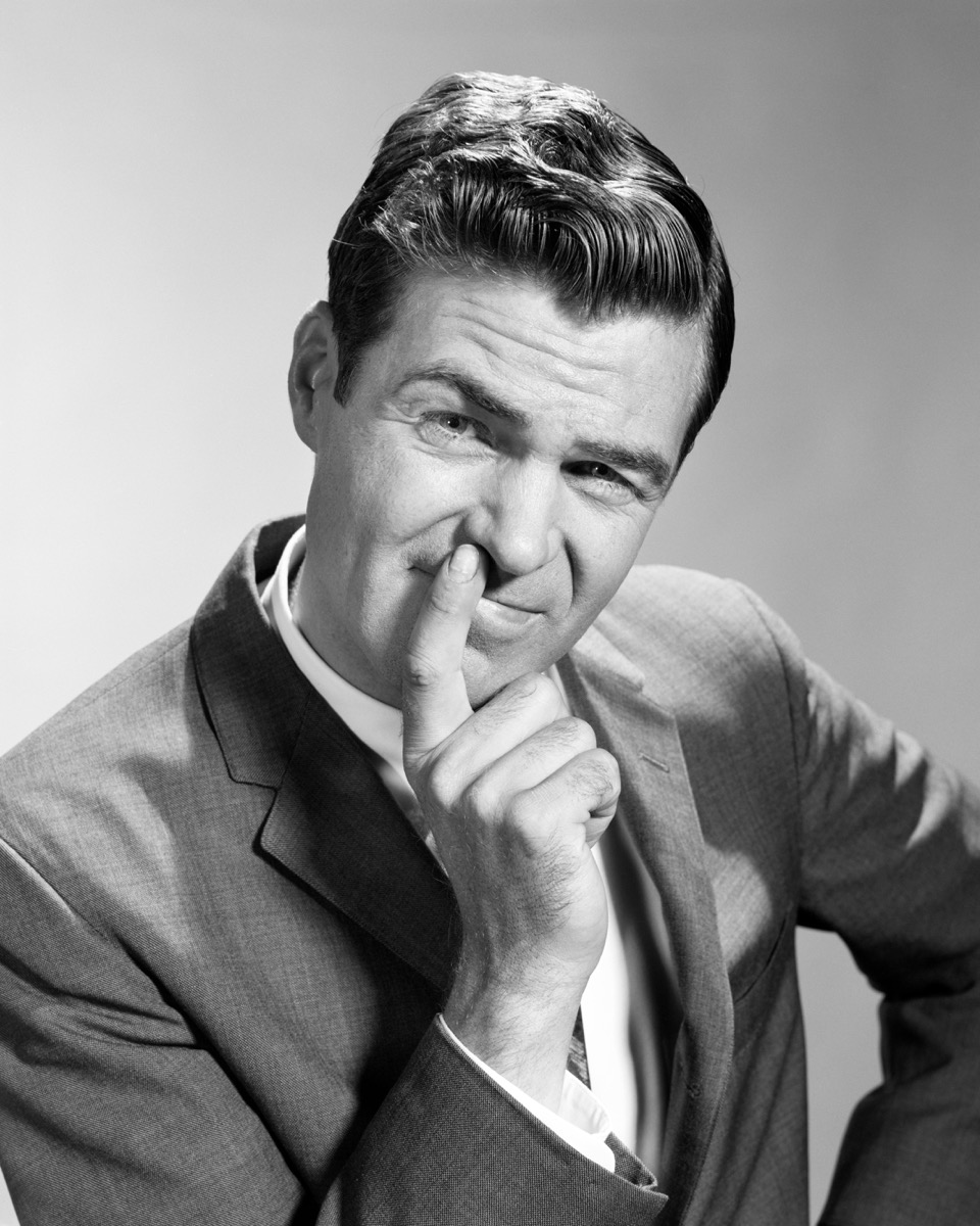 1960s man has hands on mouth, looks disgusted