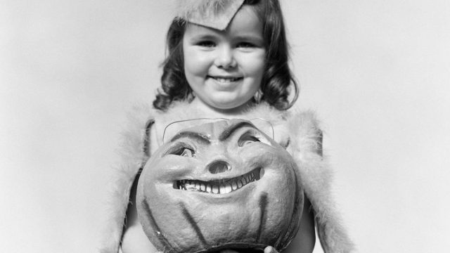 vintage halloween photo of a girl and her pumpkin