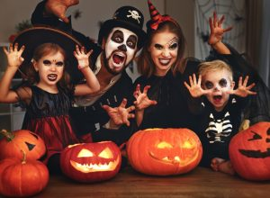 Family celebrating Halloween in traditional witch, skeleton costumes, with pumpkins in front of them