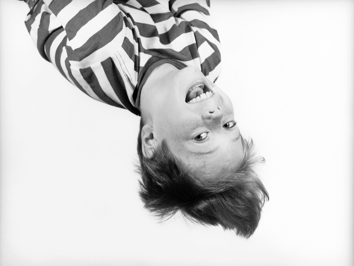 1950s BOY IN STRIPED T-SHIRT HANGING UPSIDE-DOWN