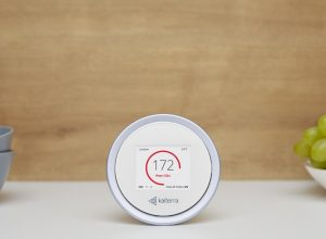 white circular air quality monitor device in front of brown wall