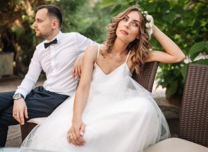 Newlywed bride and groom sitting on a sofa angry at each other in a middle of an argument.