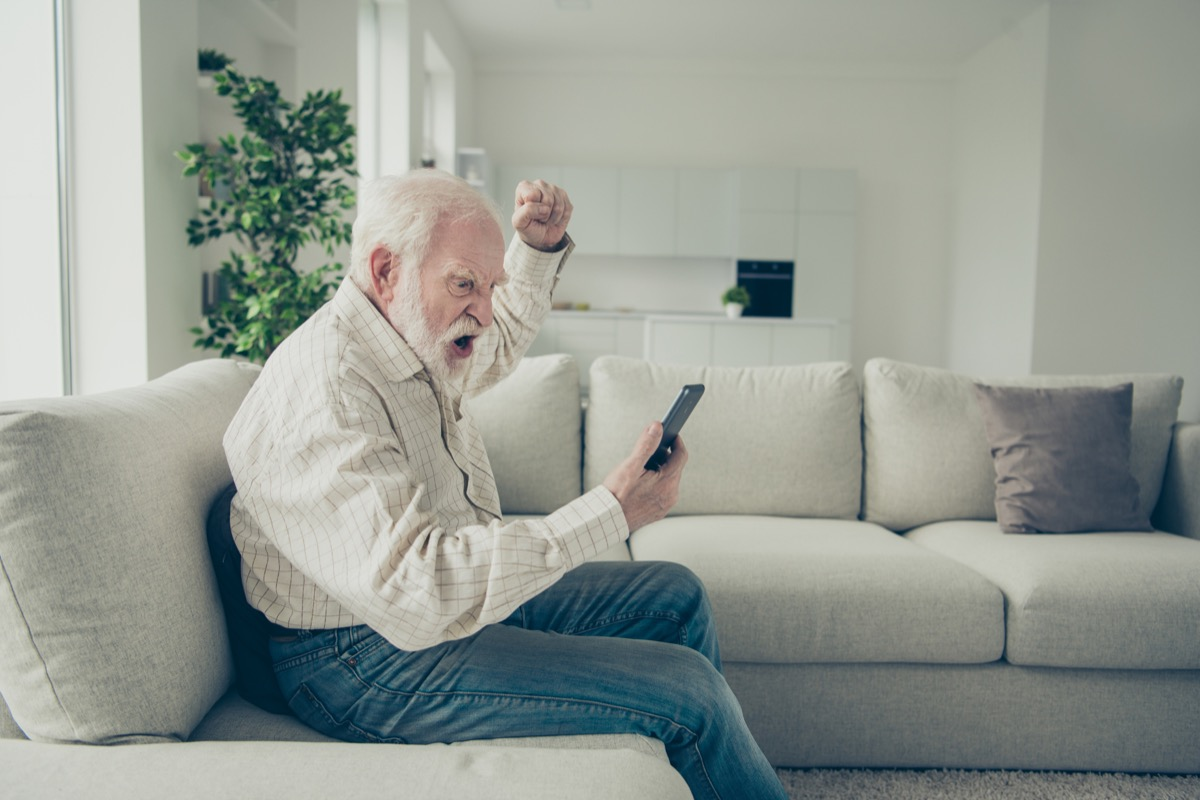 Profile side view portrait of mad stylish old man wearing checked shirt sitting on divan holding in hand phone going crazy resenting in white light modern interior studio (Profile side view portrait of mad stylish old man wearing checked shirt sitting