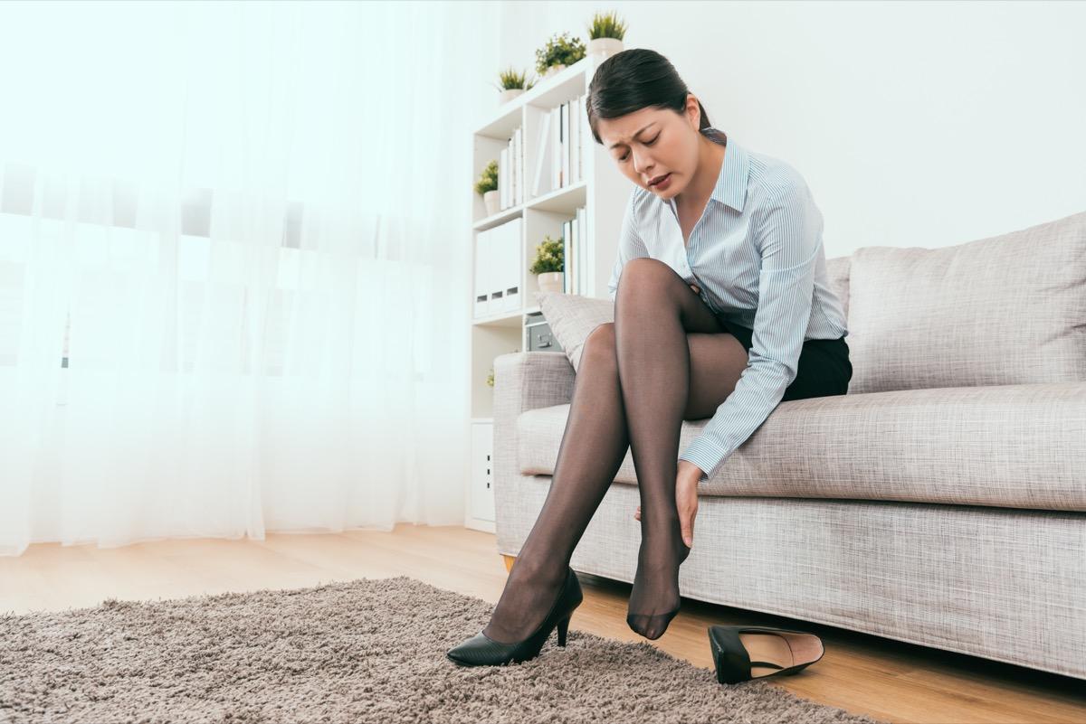 Asian woman rubbing her heel in pain