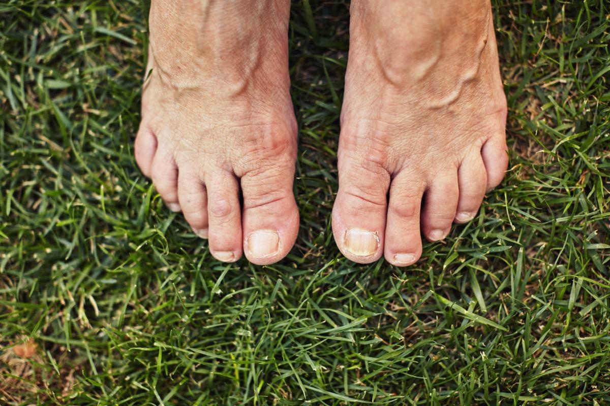 Barefoot senior standing on the green grass