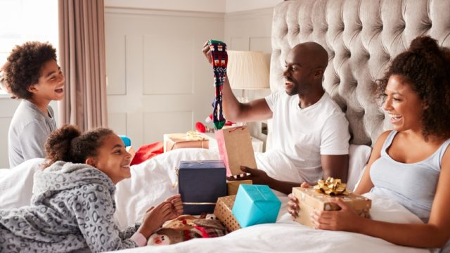 black woman, man, and two children opening presents in bed