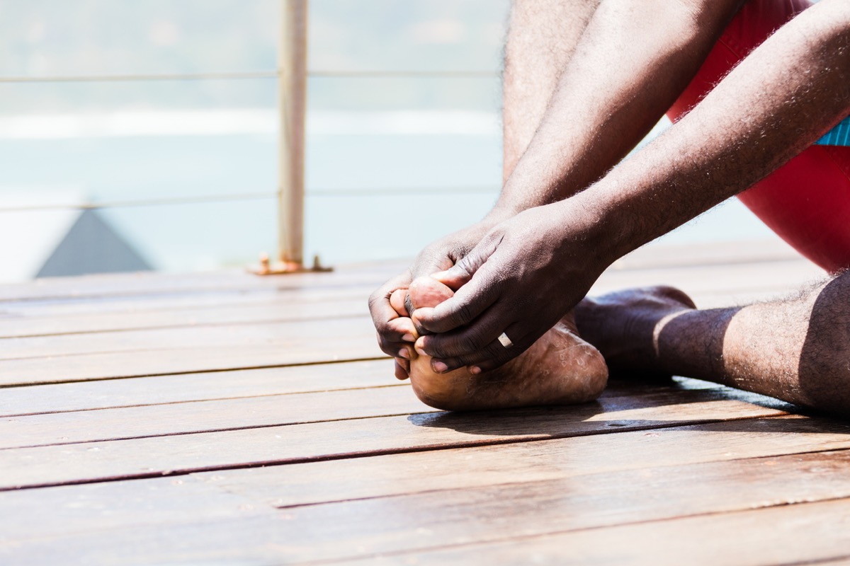 An African person gripping his big toe