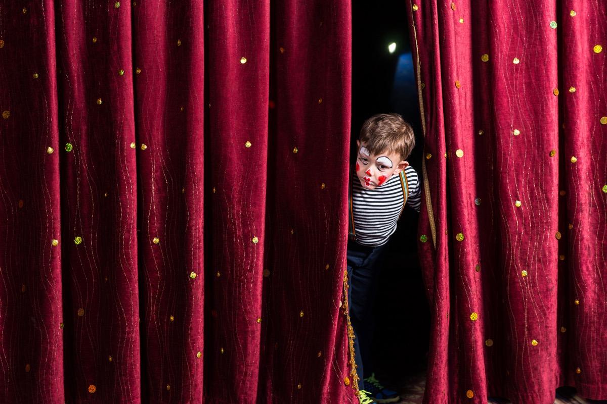 boy peeking through stage curtains