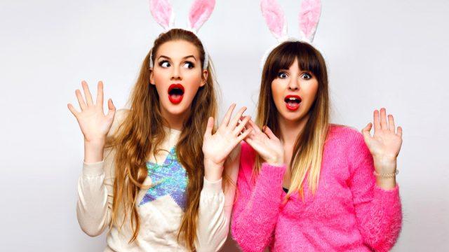 Two women taking a photograph wearing bunny ears