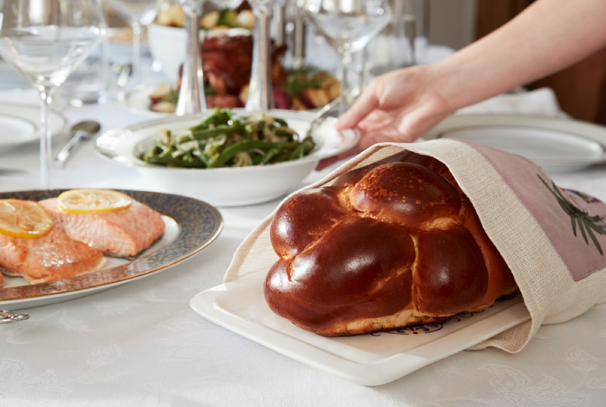 woman placing challah and vegetables on seder table, rosh hashanah facts