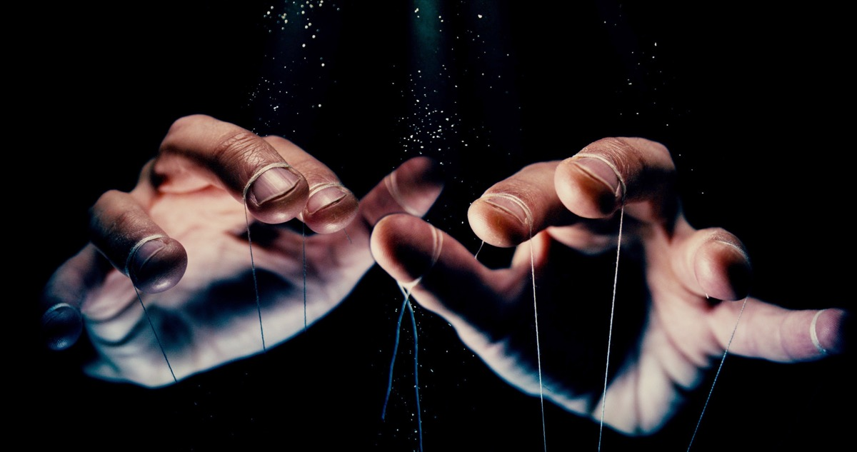 control concept photo with black background shows hands with strings tied to them, like a puppet master