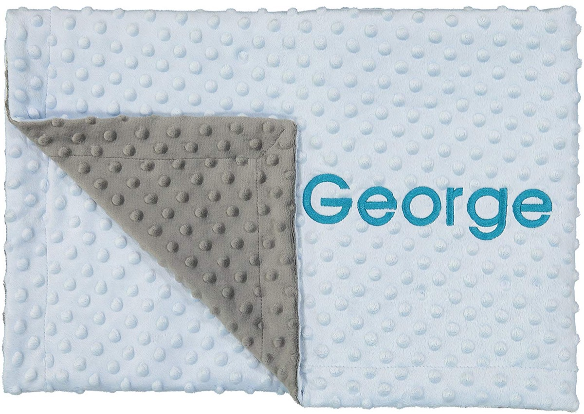 """blue nubbly baby blanket with """"george"""" embroidered on it in blue"""