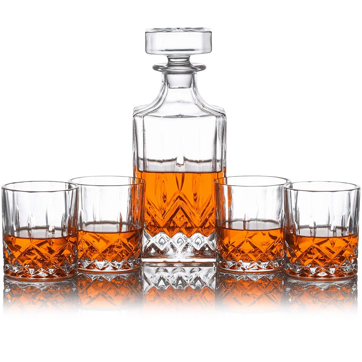 glass decanter and four cups with whiskey in them